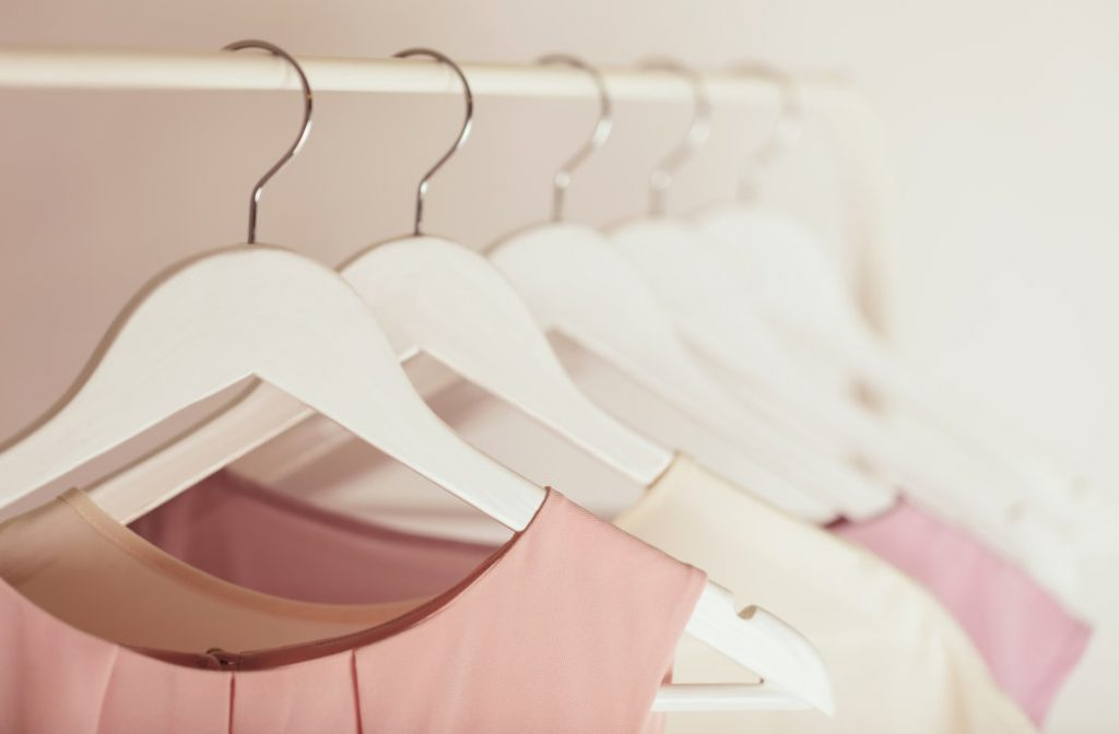 Women's clothing in pink tones on a white hanger.